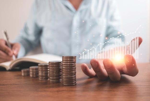 Geschäftsmann, der virtuelles diagramm hält und spart dividende oder gewinn auf notizbuch mit stapeln von münzen schreibt. konzept für unternehmensinvestitionen und gewinneinsparungen.