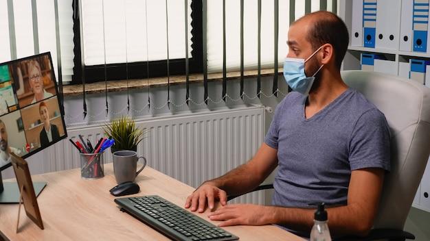 Geschäftsmann, der vor dem computer in einem neuen normalen büro sitzt und einen videoanruf mit schutzmaske hat. freiberufler, der das chatten während einer virtuellen konferenz, eines meetings unter verwendung der internettechnologie bespricht.