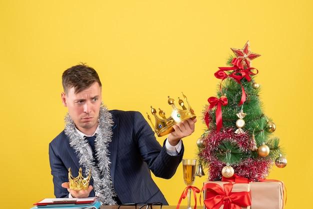 Geschäftsmann der vorderansicht, der seine kronen vergleicht, die am tisch nahe weihnachtsbaum sitzen und auf gelbem hintergrund präsentieren