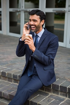 Geschäftsmann, der wegwerfbare kaffeetasse hält, die auf mobiltelefon im konferenzzentrum spricht