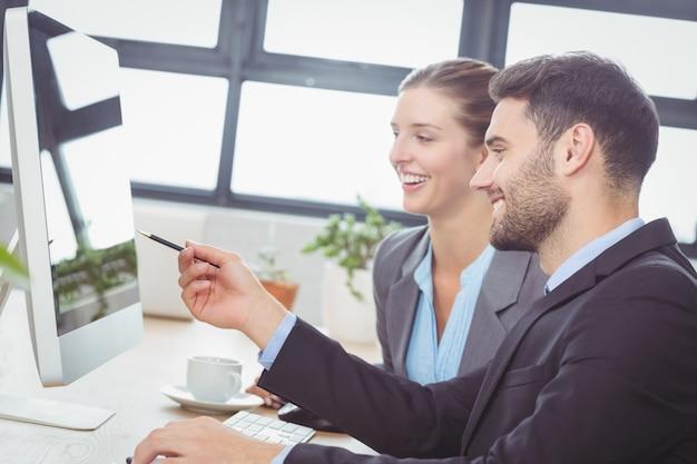 Geschäftsmann, der weiblichen kollegen am computertisch erklärt