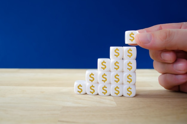 Geschäftsmann, der weiße würfel mit golddollarzeichen in einer form des wachstumsgraphen in einem konzeptuellen bild des finanziellen wachstums zusammensetzt.