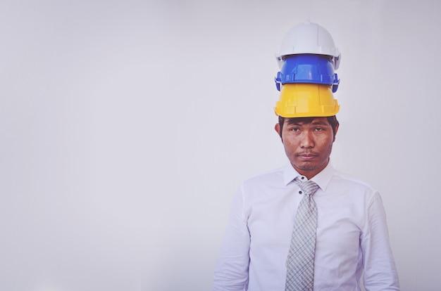 Geschäftsmann, der weißen blauen gelben sturzhelm trägt