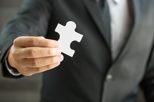 Geschäftsmann, der weißes puzzleteil hält