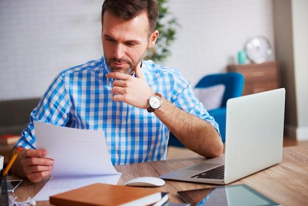 Geschäftsmann, der wichtige dokumente an seinem schreibtisch liest