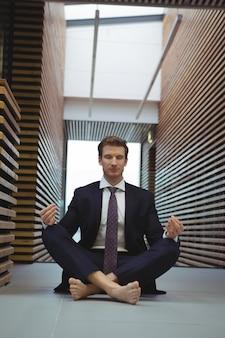 Geschäftsmann, der yoga im korridor durchführt
