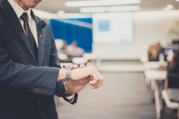 Geschäftsmann, der zeit im firmenkundengeschäftkonferenzraum überprüft. publikum im konferenzsaal. veranstaltung für business und entrepreneurship.