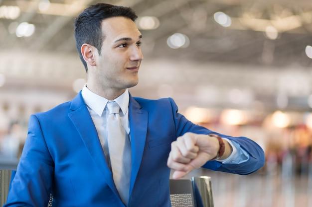 Geschäftsmann, der zeit im flughafen, flugverzögerungskonzept überprüft