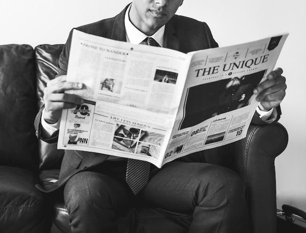 Geschäftsmann, der zeitung sitzt und liest
