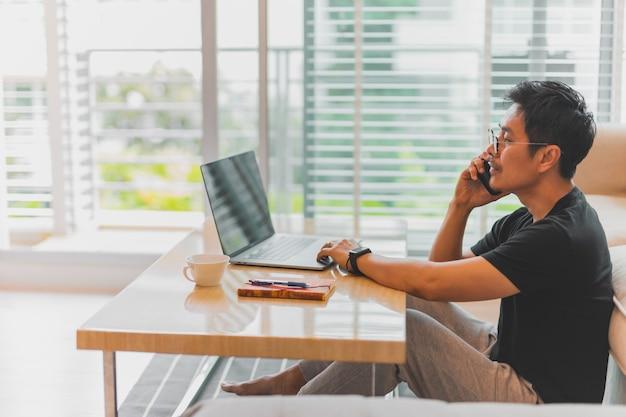 Geschäftsmann, der zu hause auf dem boden sitzt und einen anruf hat, während er am laptop arbeitet