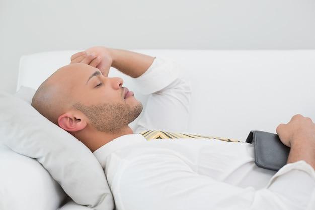 Geschäftsmann, der zu hause auf sofa mit digitaler tablette schläft