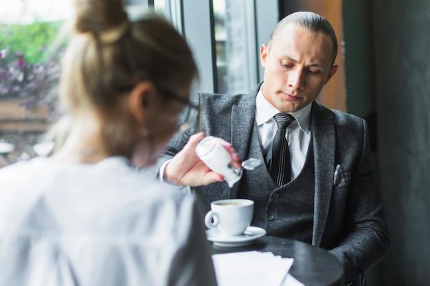 Geschäftsmann, der zucker im kaffee hinzufügt