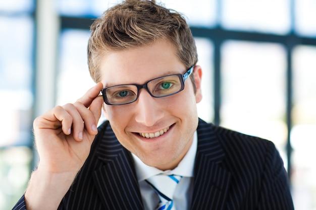 Geschäftsmann, der zur tragenden brille der kamera schaut
