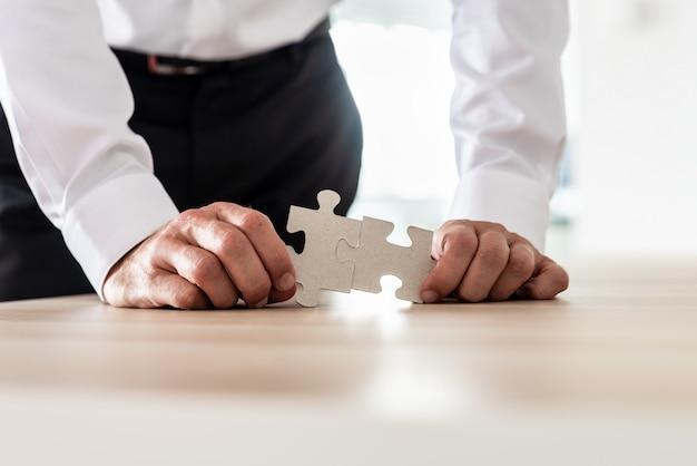 Geschäftsmann, der zwei passende puzzleteile verbindet
