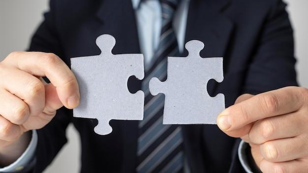 Geschäftsmann, der zwei puzzleteile hält