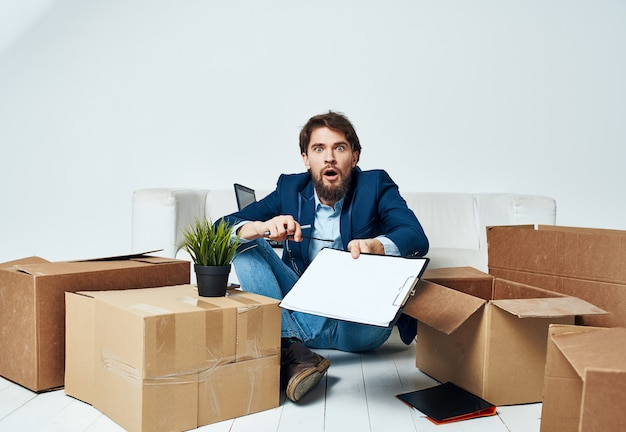 Geschäftsmann dokumentiert kisten, die professionelles büro auspacken.