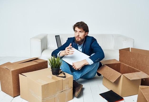 Geschäftsmann dokumentiert kisten mit dingen, die büroleiter auspacken