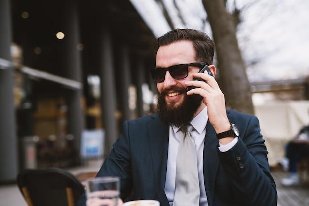Geschäftsmann draußen, der pause am kaffeehaus macht.