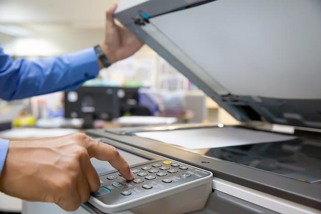Geschäftsmann drücken knopf mit fotokopierer im büroarbeitsplatz