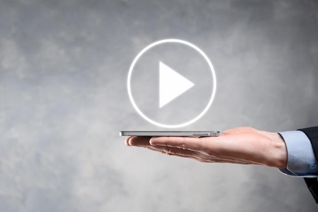 Geschäftsmann drücken, play-button-zeichen gedrückt halten, um projekte zu starten oder zu initiieren. video-play-präsentation. idee für unternehmen, technology.media player-schaltfläche. spielen sie icon.go.