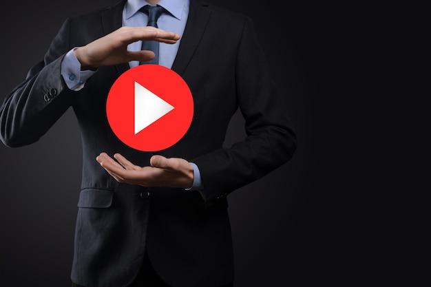 Geschäftsmann drücken, play-button-zeichen gedrückt halten, um projekte zu starten oder zu initiieren. video-play-präsentation. idee für unternehmen, technology.media player-taste. spielen sie icon.go.