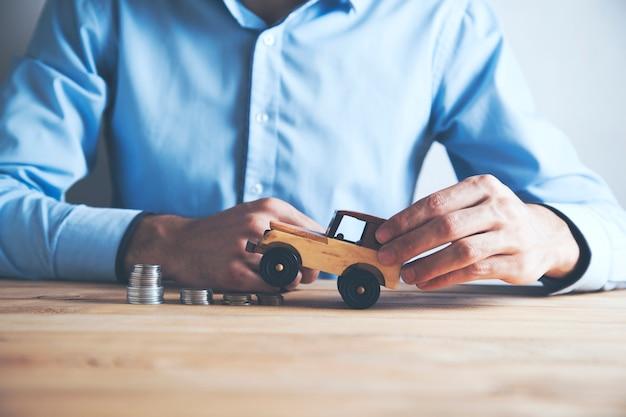 Geschäftsmann ein spielzeugauto und ein stapel münzen