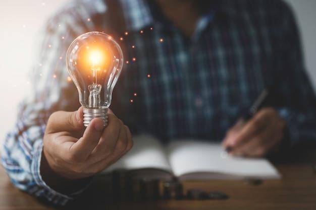 Geschäftsmann eine hand hält glühbirne mit orange leuchtendem und eine hand, die kreative idee zum notizbuch schreibt.
