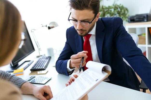 Geschäftsmann erklärt vertragsbedingungen an seine kunden im büro.