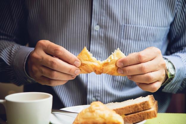 Geschäftsmann essen das amerikanische frühstück, das in ein hotel eingestellt wird
