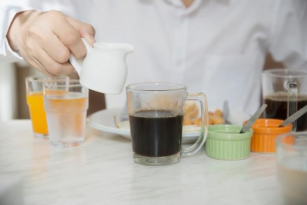 Geschäftsmann essen das amerikanische frühstück, das in einem hotel eingestellt wird