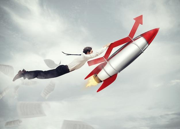 Geschäftsmann fliegt befestigt an einer rakete mit einem pfeil. start geschäftserfolgskonzept. 3d-rendering