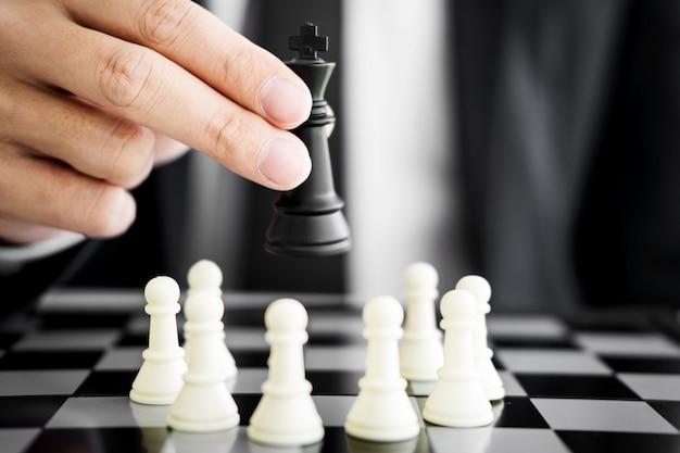 Geschäftsmann führer eines erfolgreichen geschäfts halten das schach in der hand digital composite von schach stücke