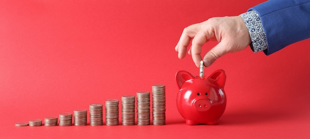 Geschäftsmann füllt sparschwein mit dollar-banknote neben dort stapeln von münzen auf rotem hintergrund. banksparanlage und einlagenkonzept.