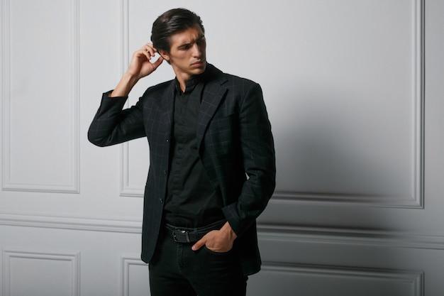 Geschäftsmann gekleidet im schwarzen anzugporträt gegen einen weißen hintergrund. porträt hübscher junger mann, der zur seite schaut.