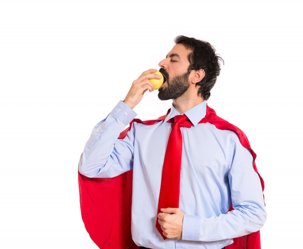 Geschäftsmann gekleidet wie superheld essen einen apfel