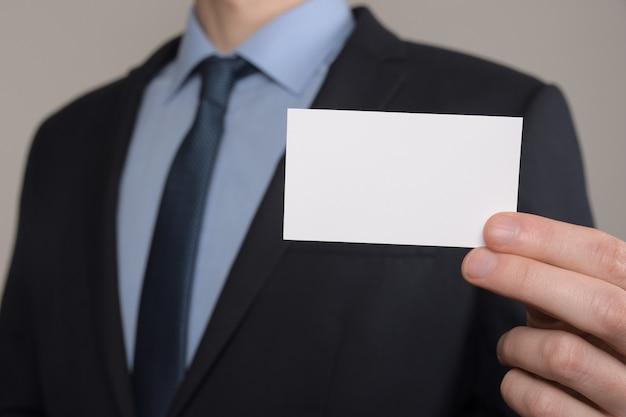 Geschäftsmann, geschäftsmanns handgriff, der visitenkarte zeigt - nahaufnahmeaufnahme auf grauer wand. zeigen sie ein leeres stück papier. visitenkarte aus papier.