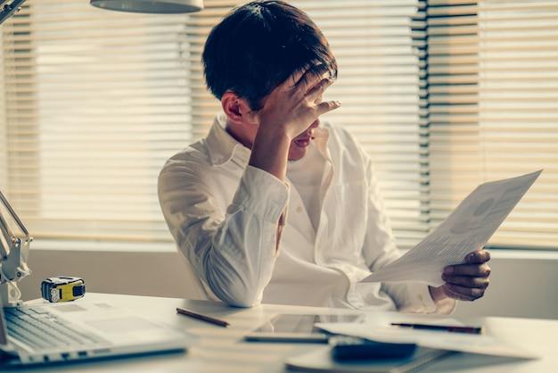 Geschäftsmann gestresst und besorgt über die späte zeit, um das arbeitsprojekt zu beenden