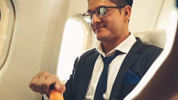 Geschäftsmann haben orangensaft von einer stewardess im flugzeug serviert