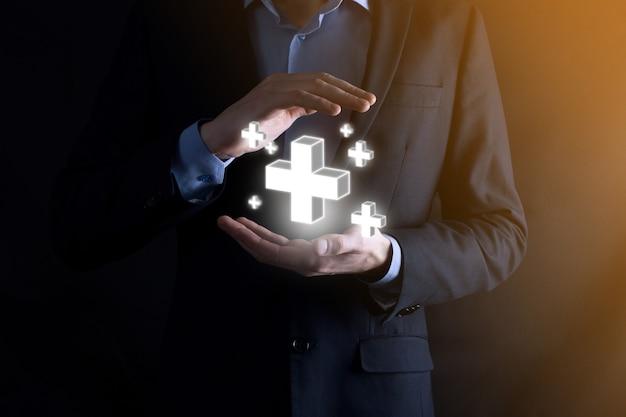 Geschäftsmann hält 3d-plus-symbol, mann hält in der hand und bietet positive dinge wie gewinn, vorteile, entwicklung, csr, dargestellt durch pluszeichen. die hand zeigt das pluszeichen.