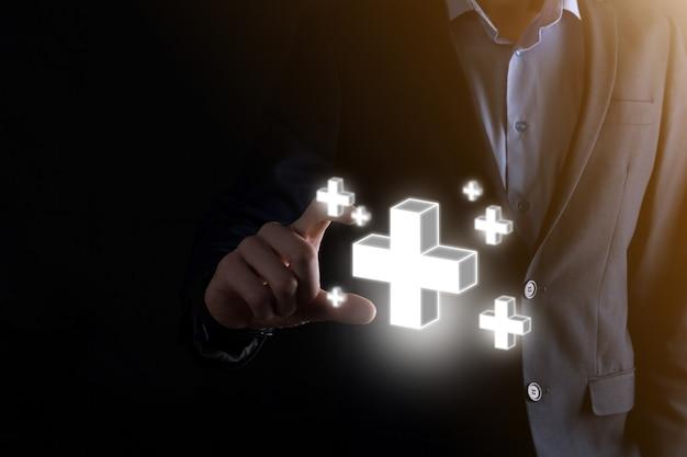Geschäftsmann hält 3d-plus-symbol, mann hält in der hand und bietet positive dinge wie gewinn, vorteile, entwicklung, csr, dargestellt durch pluszeichen. die hand zeigt das pluszeichen