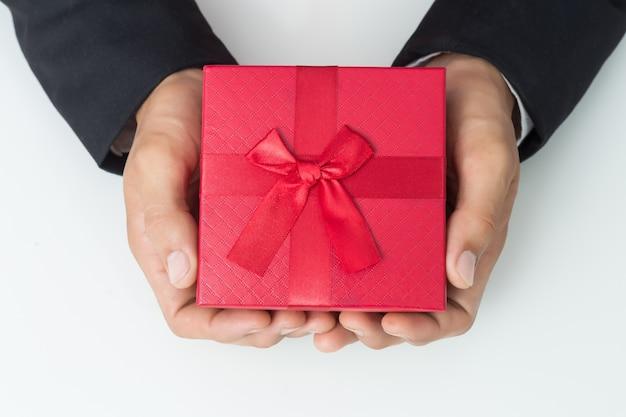 Geschäftsmann hält den roten kasten des geschenks, lokalisierten hintergrund aus