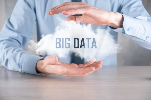 Geschäftsmann hält die aufschrift big data. vorhängeschloss, gehirn, mann, planet, diagramm, lupe, zahnräder, wolke, gitter, dokument, brief, telefonsymbol.