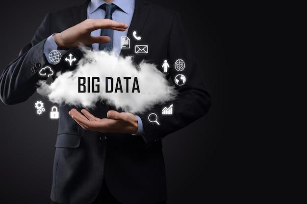 Geschäftsmann hält die aufschrift, wort big data. vorhängeschloss, gehirn, mann, planet, diagramm, lupe, zahnräder, wolke, gitter, dokument, brief, telefonsymbol.