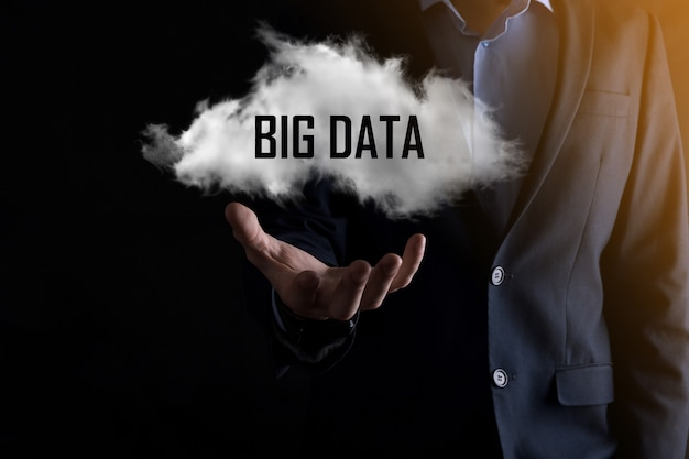 Geschäftsmann hält die inschrift big data. vorhängeschloss, gehirn, mensch, planet, grafik, lupe, zahnräder, wolke, gitter, dokument, brief, telefonsymbol.