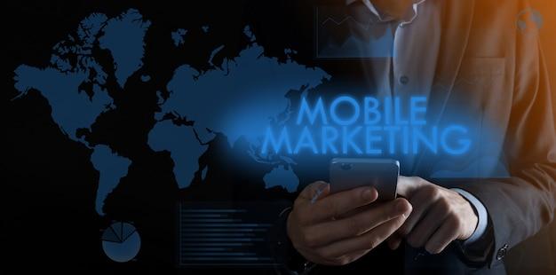 Geschäftsmann hält ein smartphone mit der aufschrift mobile marketing mit verschiedenen grafiken und weltma.m-banking und omni-kanal, online-shopping.