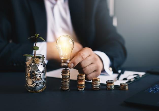 Geschäftsmann hält eine glühbirne mit münzenstapel und glas mit grüner pflanze
