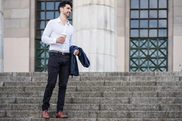 Geschäftsmann hält eine tasse kaffee auf dem weg zur arbeit im freien