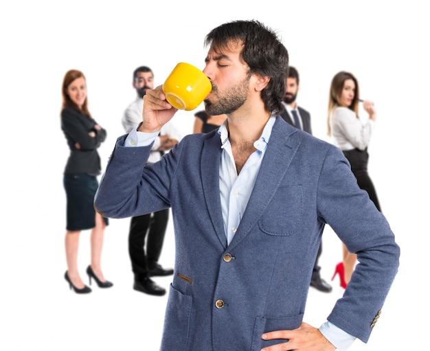 Geschäftsmann hält eine tasse kaffee auf weißem hintergrund