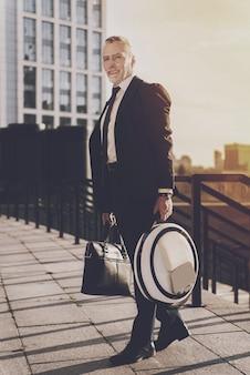 Geschäftsmann hält einen aktenkoffer und ein monowheel Premium Fotos