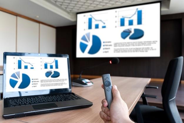 Geschäftsmann hält fernbedienungsfolie mit mock-up-diagrammpräsentation auf display-laptop und bildschirm